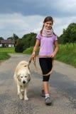 Menina que anda seu cão Fotografia de Stock