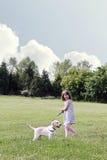 Menina que anda seu filhote de cachorro fotografia de stock