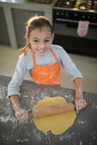 Menina que aplaina a massa no contador de cozinha Fotografia de Stock Royalty Free