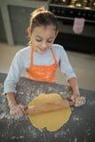 Menina que aplaina a massa no contador de cozinha Imagem de Stock