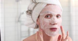 Menina que aplica a máscara em sua cara que olha no espelho filme
