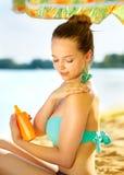 Menina que aplica o creme do bronzeado em sua pele Fotos de Stock Royalty Free