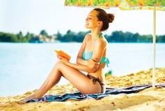 Menina que aplica o creme do bronzeado em sua pele na praia Imagens de Stock