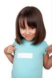 Menina que aponta à etiqueta branca em sua camisa imagens de stock