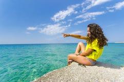 Menina que aponta ao horizonte do oceano Fotografia de Stock Royalty Free