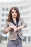 Menina que aponta em seu relógio Foto de Stock Royalty Free
