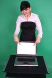 Menina que aponta na tela em branco do portátil. Fotos de Stock