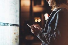 Menina que aponta o dedo no smartphone da tela na caixa leve do fundo no mapa atmosférico da cidade da noite, moderno que usa-se  imagem de stock royalty free