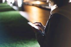Menina que aponta o dedo no smartphone da tela na luz na cidade atmosférica da noite, utilização da cor do bokeh da iluminação do fotos de stock royalty free