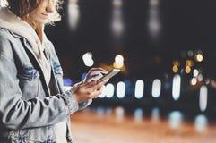 Menina que aponta o dedo no smartphone da tela na luz na cidade atmosférica da noite, utilização da cor do bokeh da iluminação do foto de stock royalty free