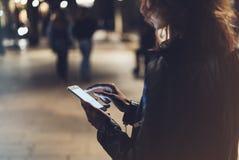 Menina que aponta o dedo no smartphone da tela na luz na cidade atmosférica da noite, utilização da cor do bokeh da iluminação do fotografia de stock
