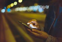 Menina que aponta o dedo no smartphone da tela na luz na cidade atmosférica da noite, utilização do bokeh do fulgor da iluminação foto de stock