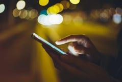 Menina que aponta o dedo no smartphone da tela na luz na cidade atmosférica da noite, utilização do bokeh do fulgor da iluminação fotografia de stock