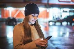 Menina que aponta o dedo no smartphone da tela na luz da cor do bokeh da iluminação do fundo na cidade atmosférica da noite Fotografia de Stock Royalty Free