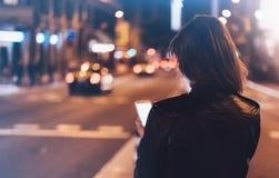Menina que aponta o dedo no smartphone da tela na luz do bokeh do fulgor da iluminação do fundo na cidade atmosférica da noite, u fotos de stock