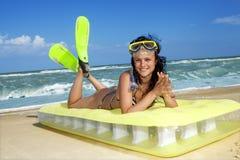 Menina que aprecia em um colchão inflável da praia imagem de stock