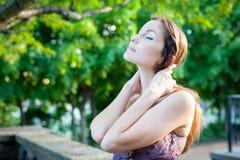 Menina que aprecia a luz do sol no parque fotos de stock royalty free