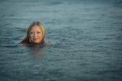 Menina que aprecia o banho em uma água azul Foto de Stock