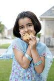 Menina que aprecia o bolinho Fotos de Stock Royalty Free