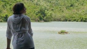 A menina que aprecia o rio e a montanha bonitos da paisagem cobriu a jovem mulher verde da floresta que olha na água e no verde d filme