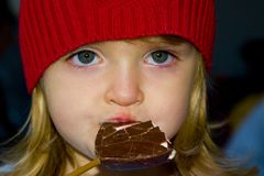 Menina que aprecia um chocolate Imagem de Stock