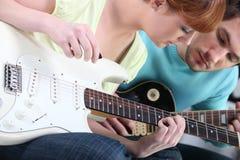 Menina que aprende jogar a guitarra Fotos de Stock Royalty Free