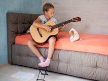 Menina que aprende jogar um instrumento musical fotografia de stock