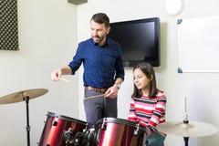 Menina que aprende lições de rufar na classe de música imagens de stock royalty free