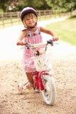 Menina que aprende montar o capacete de segurança desgastando da bicicleta Fotos de Stock
