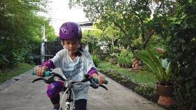 Menina que aprende montar uma bicicleta no quintal vídeos de arquivo