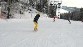 Menina que aprende montar uma inclinação em declive em um snowboard A moça aprende ao snowboard Câmera no movimento video estoque