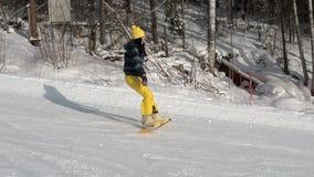 Menina que aprende montar uma inclinação em declive em um snowboard A moça aprende ao snowboard Câmera no movimento Povos sobre vídeos de arquivo