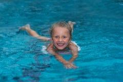 Menina que aprende nadar na associação grande do esporte Escola da natação para crianças pequenas Criança saudável que aprecia o  Foto de Stock