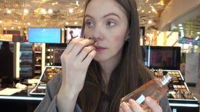 Menina que aspira a loja agradável da beleza do cheiro do perfume video estoque