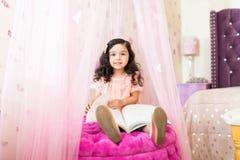 Menina que atravessa o livro em Seat na princesa Bedroom foto de stock