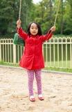 Menina que balança no campo de jogos Foto de Stock Royalty Free