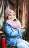 Menina que bebe o chá quente da garrafa térmica foto de stock