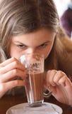 Menina que bebe seu latte do café Imagens de Stock