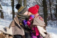 Menina que beija o menino com presente fora imagem de stock royalty free