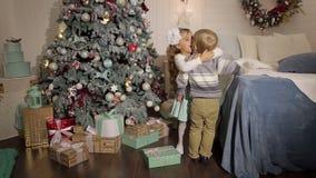 Menina que beija o rapaz pequeno perto da árvore de Natal vídeos de arquivo