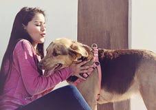 Menina que beija seu cão Fotografia de Stock