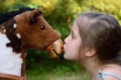 Menina que beija um cavalo de balanço Imagens de Stock Royalty Free