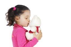 Menina que beija um urso de peluche Fotografia de Stock Royalty Free