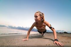A menina que bonito do ajuste fazer empurra levanta na praia no nascer do sol Foto de Stock Royalty Free