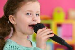 Menina que canta com microfone Fotos de Stock