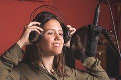 Menina que canta com um microfone e os fones de ouvido fotografia de stock royalty free
