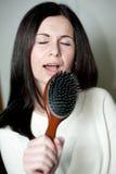 Menina que canta na escova de cabelo Imagens de Stock Royalty Free