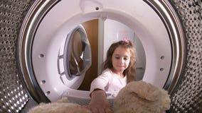 Menina que carrega seu brinquedo enchido à máquina de lavar vídeos de arquivo