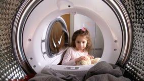 Menina que carrega seu brinquedo enchido à máquina de lavar video estoque