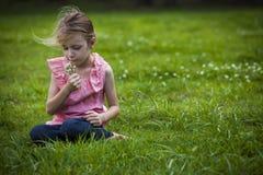 Menina que cheira Flowoers selvagem Fotografia de Stock Royalty Free